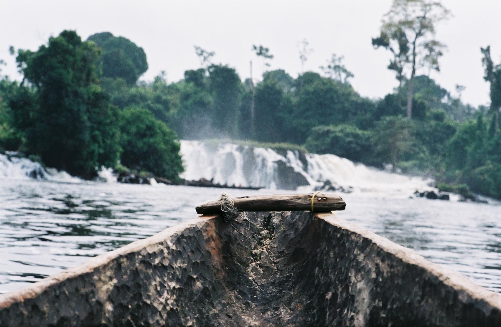 pirogue remontant le fleuve Lobe, au loin les chutes eponymes Kribi region du sud Cameroun
